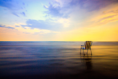 An empty chair facing the ocean